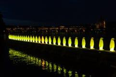 PRAG, TSCHECHISCHE REPUBLIK - 16. Juli 2017: Riesige Stuhl-Skulptur und Pinguin-Skulptur nachts auf der Bank von Fluss Lizenzfreies Stockbild