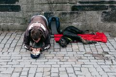 Praga 08 13 2017 Bezdomny młody człowiek pyta passersby dla pieniądze z dużym czarnym psem na ulicie Zdjęcie Royalty Free
