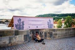 Praga 13 08 2013 Bezdomny młody człowiek pyta passersby dla pieniądze z dużym czarnym psem na ulicie editorial Obraz Royalty Free