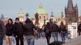 PRAGA, CECHIA - 9 APRILE 2019: I turisti attraversano Charles Bridge - sera tardi - il tramonto iniziale, aprile 2019 stock footage