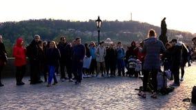 PRAGA, CZECHIA - 10 DE ABRIL DE 2019: Los turistas escuchan un juego de la banda en el puente famoso de Chales durante puesta del metrajes