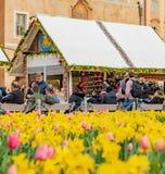 PRAGA, CZECHIA - 10 DE ABRIL DE 2019: Muchedumbres en el mercado de Pascua en la vieja plaza de Praga rodeada por los narcisos de fotos de archivo libres de regalías