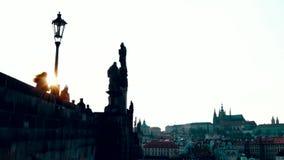PRAGA, CZECHIA - 12 DE ABRIL DE 2019: Turistas en Charles Bridge famoso durante puesta del sol temprana durante los días de fies almacen de metraje de vídeo