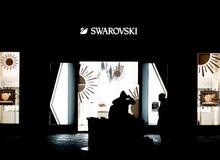 PRAGA, CZECHIA - 10 DE ABRIL DE 2019: Um par senta-se na frente de uma loja de Swarovski tarde na noite em Praga imagens de stock royalty free
