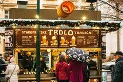 Praga, el 24 de diciembre de 2016: Praga el día de la Navidad Turistas en la compra Trdlo en la parada - comida nacional de los c imagen de archivo libre de regalías