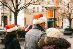 Praga, el 24 de diciembre de 2016: La Navidad en Praga - gente desconocida en los casquillos rojos de Santa Claus que camina a lo Imagen de archivo libre de regalías