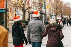 Praga, el 24 de diciembre de 2016: La Navidad en Praga - gente desconocida en los casquillos rojos de Santa Claus que camina a lo Fotografía de archivo