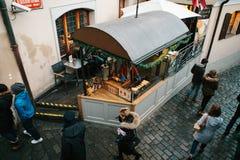 Praga, el 24 de diciembre de 2016: Turismo en Praga Visión superior - cocinero en parada de calle prepara el plato especial de Pr Imagen de archivo