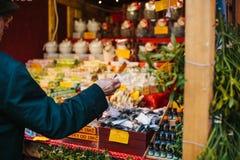 Praga, el 15 de diciembre de 2016: Un hombre mayor compra regalos de Navidad a sus nietos en el mercado de la Navidad Regalos Foto de archivo libre de regalías