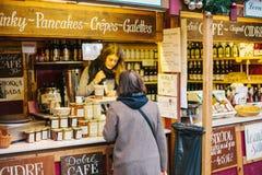 Praga, il 15 dicembre 2016: Il venditore offre al compratore un'ampia selezione di miele e di vari vini Mercato di Natale Fotografia Stock Libera da Diritti