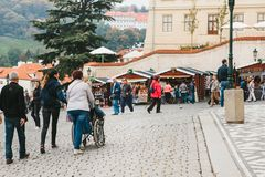 Praga, o 28 de outubro de 2017: A mulher não identificada está levando a pessoa deficiente na cadeira de rodas ao longo da rua de foto de stock
