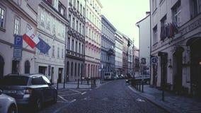 PRAGA, REPÚBLICA CHECA - 3 DE DICIEMBRE DE 2016 Calle con el polaco, las banderas de la UE y los coches parqueados Vieja opinión  fotografía de archivo