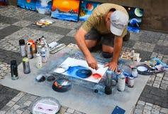 PRAGA, REPÚBLICA CHECA - 17 DE JULIO DE 2017: Un hombre pinta imágenes en la calle, usando las latas de espray de la pintura de d Imagenes de archivo