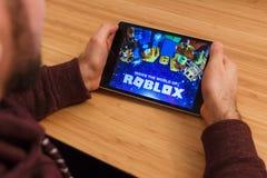 PRAGA, REPÚBLICA CHECA - 16 DE MARZO DE 2019: Hombre que lleva a cabo un smartphone y un playng el juego móvil de Roblox Un edito imagen de archivo