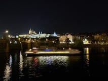 Praga, República Checa - 31 de outubro de 2018 exposição longa de um barco que cruza o rio de Vltava com vista do castelo de Prag fotos de stock royalty free
