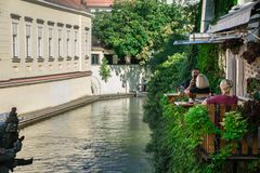 Praga, República Checa - 10 de setembro de 2019: Povos que relaxam e que almoçam nas tabelas exteriores de Velkoprevorsky Mlyn imagem de stock