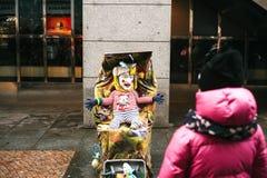 Praga, República Checa, el 24 de diciembre de 2016 - disfrazan a un payaso divertido un adulto como niño en un cochecito hospital Foto de archivo libre de regalías