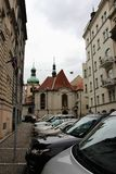 Praga, República Checa, em janeiro de 2015 Vista da rua estreita histórica com as abóbadas da catedral e dos carros estacionados fotografia de stock royalty free
