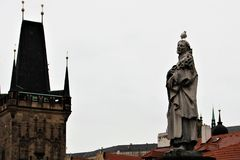 Praga, República Checa, enero de 2015 Estatua de un santo con una gaviota en su cabeza y una torre gótica fotografía de archivo libre de regalías