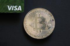 PRAGA, REPÚBLICA CHECA - mayo de 2019: Bitcoin al lado de la tarjeta de banco de la visa en fondo negro Moneda de Digitaces, merc imagenes de archivo
