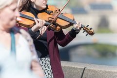 PRAGA, REP?BLICA CHECA 16-04-2019: Mulheres que jogam o violino fora entre os povos imagem de stock