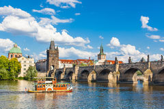Praga, repubblica Ceca, Charles Bridge attraverso il fiume della Moldava su cui la nave naviga Fotografia Stock Libera da Diritti