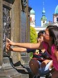 PRAGA, REPUBBLICA CECA - 29 GIUGNO 2011: Due bambini toccano il sollievo sul piedistallo di St John della statua di Nepomuk a Cha Immagine Stock