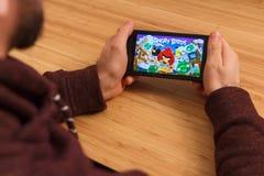 PRAGA, republika czech - MARZEC 16, 2019: Obsługuje trzymać playng i smartphone Angry Birds wiszącej ozdoby gra E fotografia royalty free