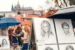 Praga, republika czech - Wrzesień 27, 2014: Uliczny portreta malarz i przykłady jego sztuka rysująca z ołówkiem Zdjęcie Stock