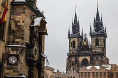 Prague astronomical clock and Church of Our Lady before Tyn. During the Winter. Snow can be seen royalty free stock images