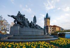 Prague astronomisk klocka bak Jan Hus Monument som omges av påskliljor i mitt av våren arkivfoton