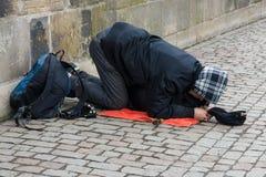 Prague. Beggar on Charles Bridge. Royalty Free Stock Images