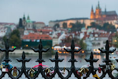 Prague behind a fence. Next to the Charles Bridge I shot this fence wih locks. In the background Prague Castle Stock Photos