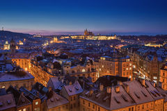 Prague castle with snow roofs and blue sky during late sunset Stock Photos