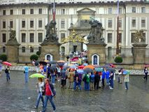 Prague Castle, Tour Group Sheltering Under Umbrellas in Rain. Tour group sheltering under colorful umbrellas in rain outside Prague Castle, Czech Republic Royalty Free Stock Image