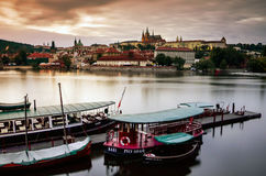 Prague castle view from the Vltava river bank, boats in front, during the dusk Stock Photo