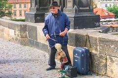 PRAGUE, CZECH - JULY 30, 2007 - An old puppet master with a puppet performing on the Charles Bridge over Vltava royalty free stock photography
