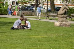 Prague, Czech Republic - April 20, 2011: These boyfriend and girlfriend are sitting on the green juicy grass royalty free stock photo