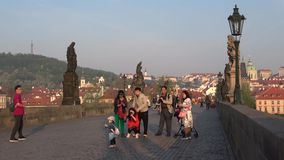 Chinese tourists on the Charles bridge, April morning. Prague, Czech Republic. Prague, Czech Republic - April 21, 2018: Chinese tourists on the Charles bridge in stock footage