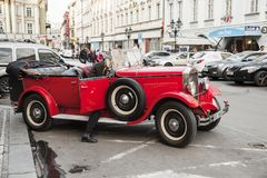 Driver gets into red vintage oldtimer car. Prague, Czech Republic - April 30, 2017: Driver gets into red vintage oldtimer car on the street of old Prague Royalty Free Stock Image