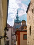 Prague, Czech republic - april 2019: Narrow ancient street, view on turquois top of St. Vitus Cathedral. Colourful. Vintage architecture of Prague. White-lilac royalty free stock photography