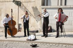 Prague, Czech Republic - April 19, 2011: Quartet of Musicians playing musical instruments for tourists on the street in Prague. Genre royalty free stock photos