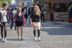Prague, Czech Republic - April 20, 2011: Three young stylish women are smiling and walking down the street royalty free stock image