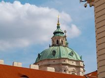 Prague, Czech republic - april 2019: View on turquois-beige top of catholic cathedral. Blue cloudy sky above top of. Christian catholic church. Cloudy spring royalty free stock image
