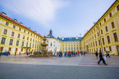 Prague, Czech Republic - 13 August, 2015: Large yellow beautiful building sorrounding square with big water fountain Stock Photography