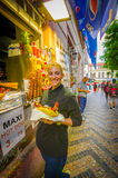 Prague, Czech Republic - 13 August, 2015: Pretty blonde local girl holding up a giant bratwurst sausage in bread Stock Image