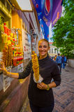Prague, Czech Republic - 13 August, 2015: Pretty blonde local girl holding up a typical potato street snack and smiling Stock Images