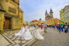Prague, Czech Republic - 13 August, 2015: Three woman wearing wedding dresses on city street with Church Of Our Lady Royalty Free Stock Photos