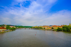 Prague, Czech Republic - 13 August, 2015: Vltava river as seen from Charles Bridge with peacful city sorrounding it. Beautiful blue sky Stock Photo