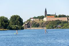 Woman sailing on standup paddleboard on Vltava river with Vysehrad in background in Prague, Czech Republic. PRAGUE, CZECH REPUBLIC - AUGUST 19 2012: Woman royalty free stock photos